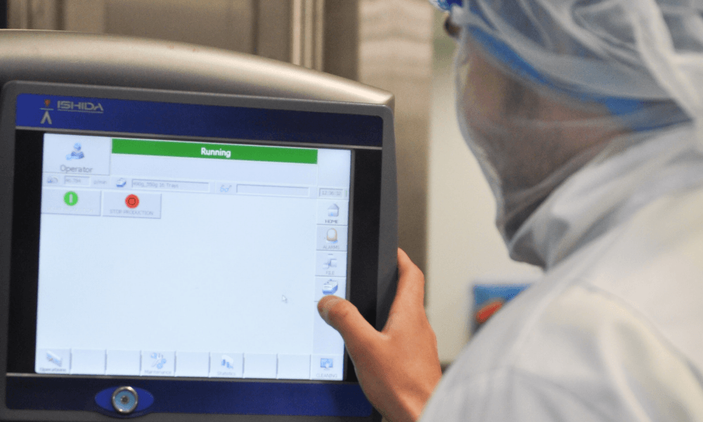 Image of man working in food processing factory inputting data on a factory floor dashboard.