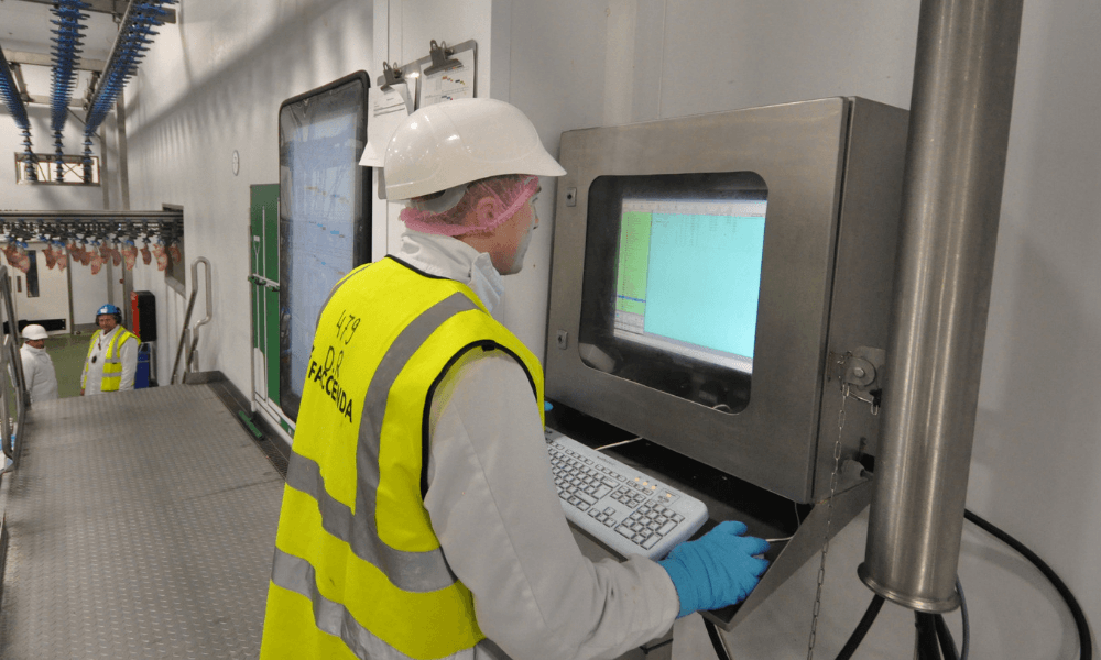 Image of man working in food processing factory reviewing real-time data on a shop floor dashboard.